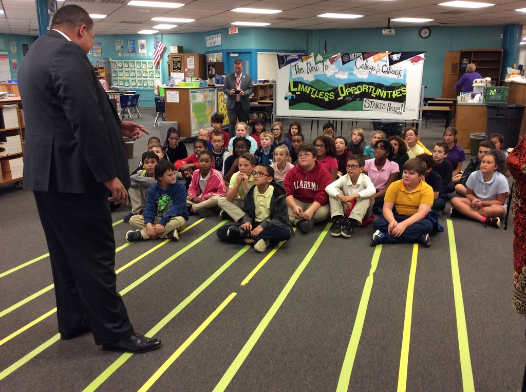 Cato 5th Grade students look on as Sheriff Higgins present Principal Lee the grant money
