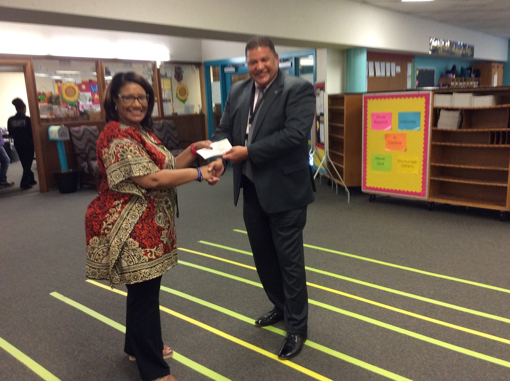 Mrs. Lee accepting the grant money from Sheriff Higgins