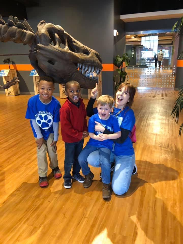 Students and teacher with dinosaur display
