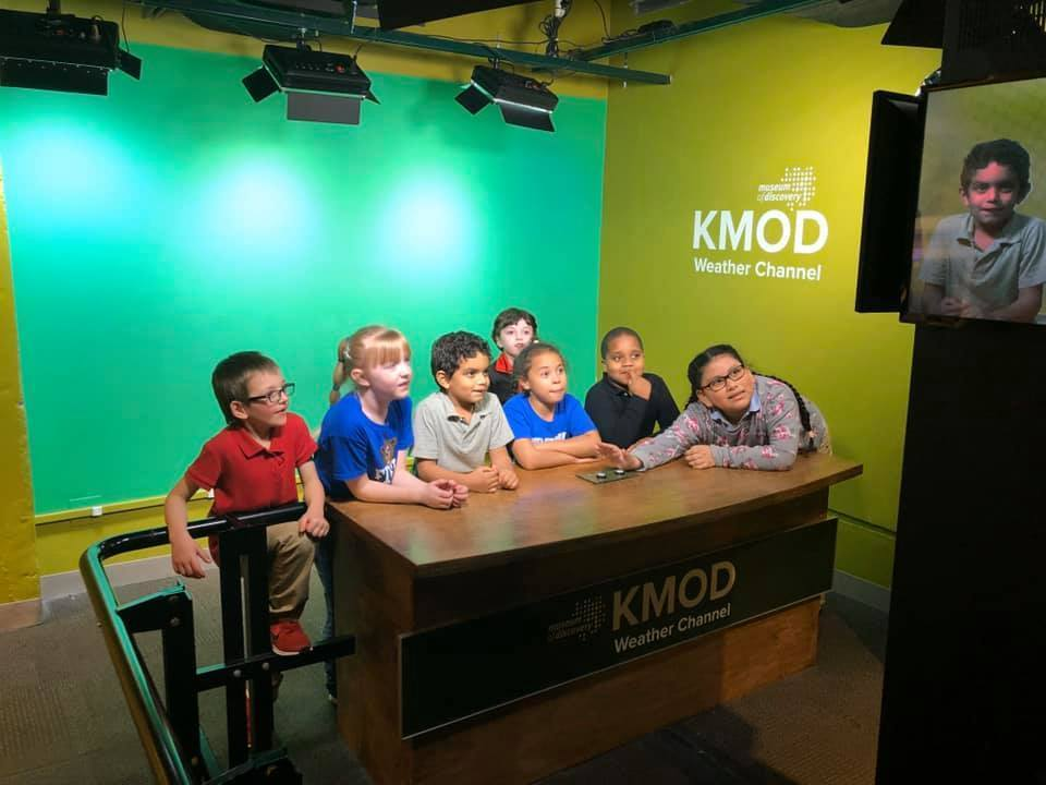Students at weather broadcasting desk museum installation